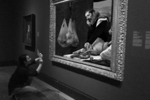 A visitor interacts with a painting
